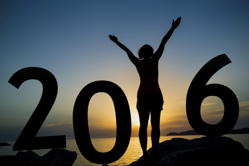 Happy new 2016 year card. A girl standing on a beach, watching the sunset, standing as a part of 2016 sign