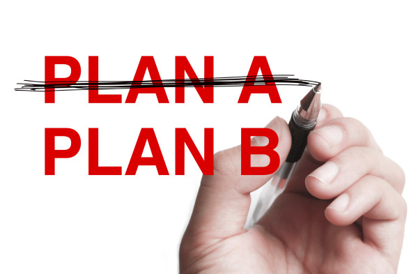 """Hand with pen is writing """" Business Plan"""" on transparent white board."""